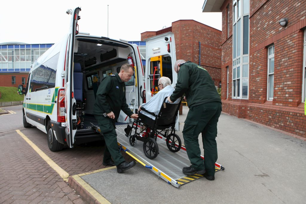 Ambulance staff pushing man in wheelchair in to ambulance.
