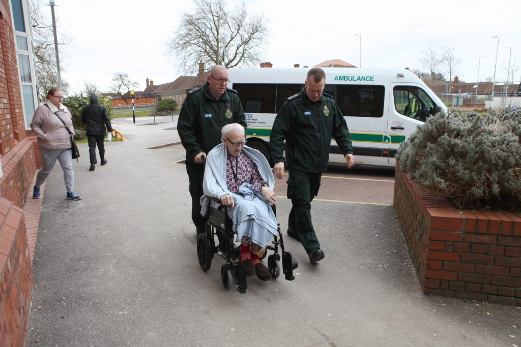 Ambulance staff pushing man in wheelchair.