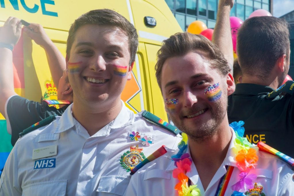 Two male staff smiling at PRIDE.