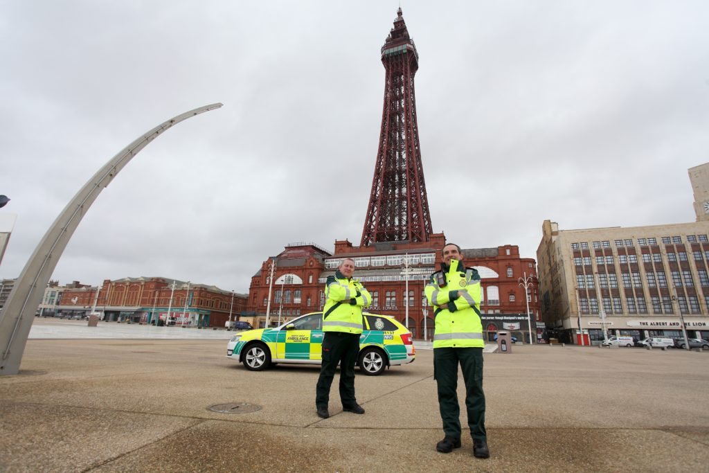 Two male staff stood in front of a first response vehicle with the Blackpool Tower behind.