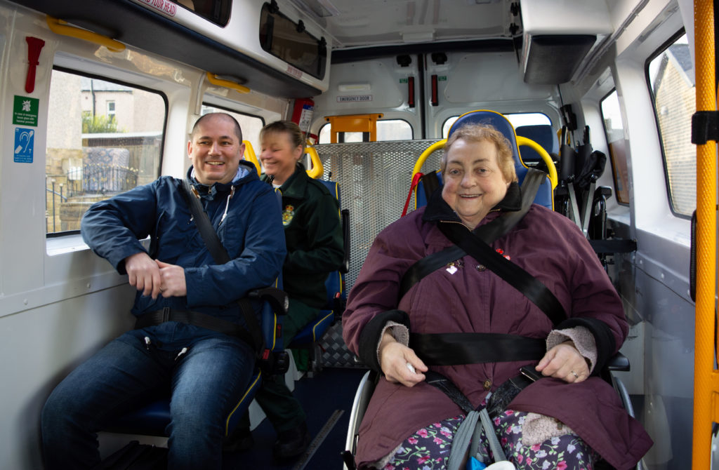 People in an Patient Transport Vehicle smiling.
