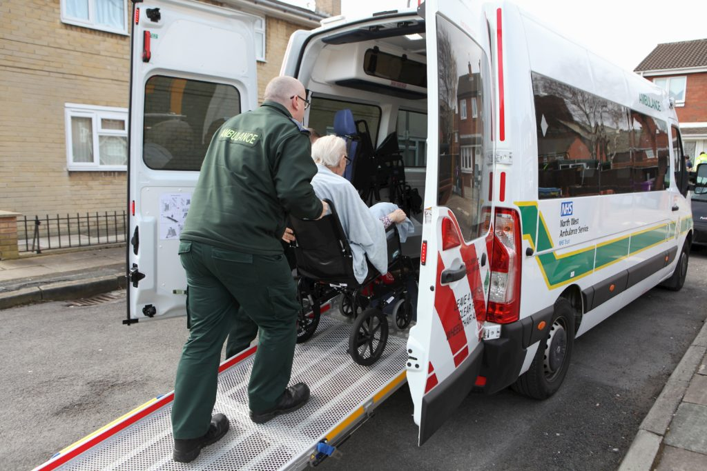 Person in wheelchair being pushed into an ambulance.