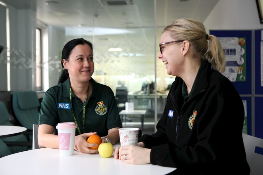 Two members of staff talking in a room.