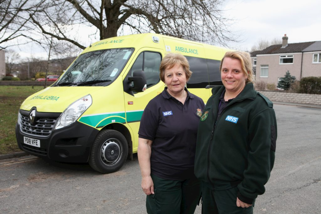 Two ladies smiling in front of an ambulance.