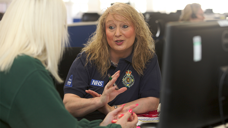 Female senior clinical advisor speaking with a colleague.