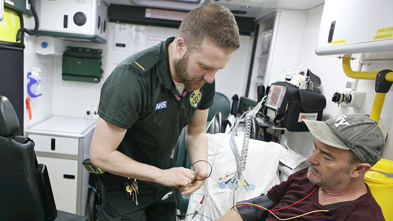 Paramedic attending to a patient inside an ambulance
