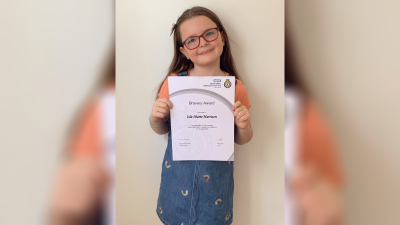Six-year-old Isla holding up her Bravery Award certificate