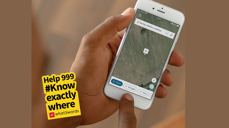 Hand holing a phone with map co-ordinates using app, what3words