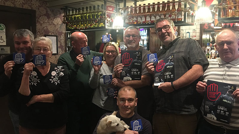 Group of people stood in pub with Calling time on violence against ambulance staff posters.