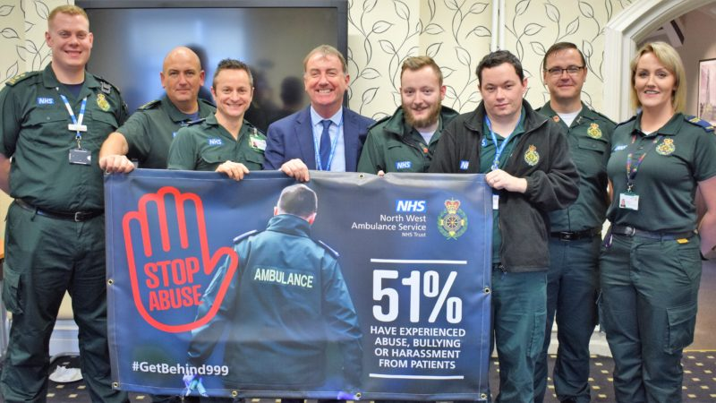 Group of staff holding stop abuse poster.