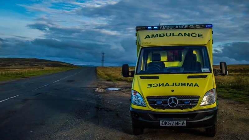Ambulance parked up on country road.