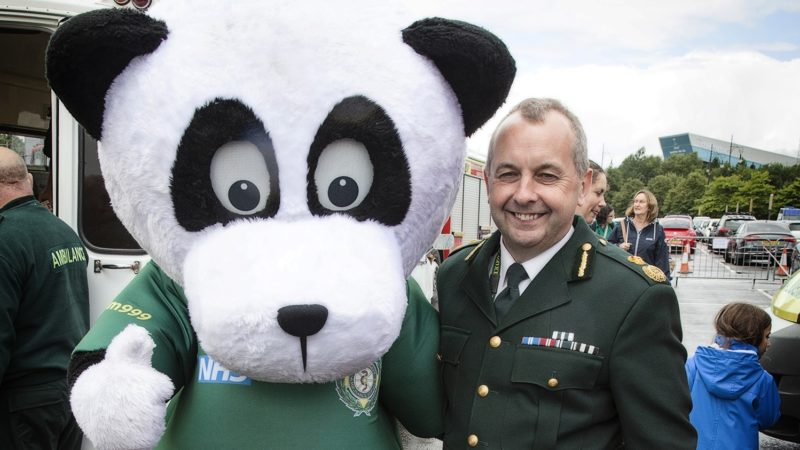 Chief executive smiling with person in Pandamedic costume.