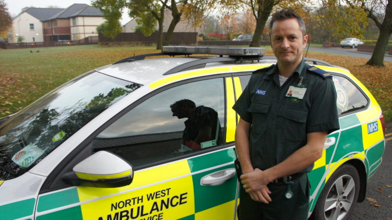 Vinny stood in front of North West Ambulance Service vehicle.