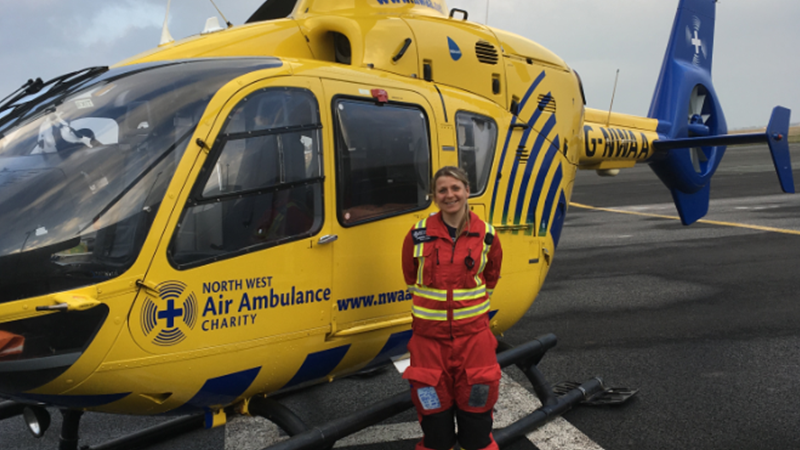 Caroline stood by a North West Air Ambulance Charity Helicopter.
