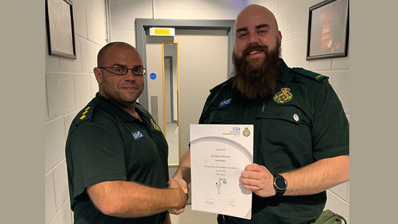 Paramedic recognised for delivering a baby with certificate and stork pin badge