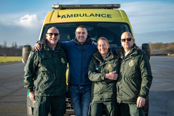 Paramedics smiling in front of ambulance with Paddy McGuinness