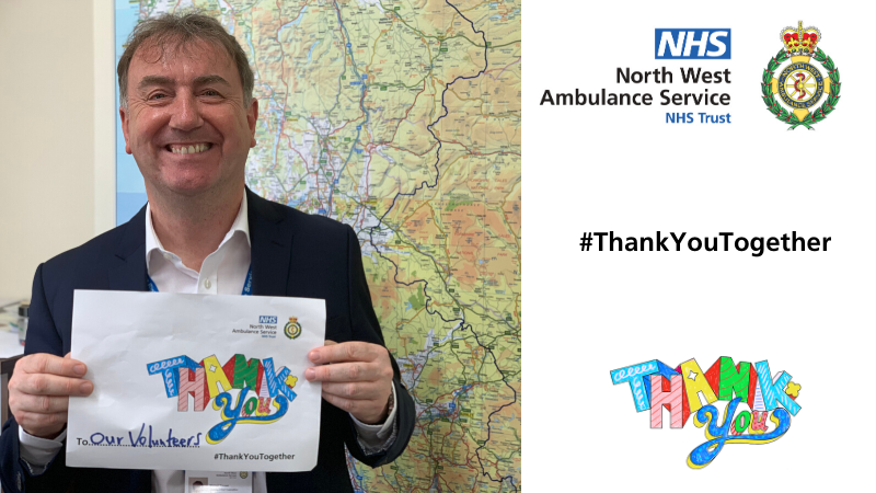 Deputy CEO Mick Forrest holding up a thank you poster dedicated to our volunteers
