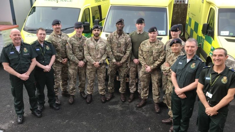 A group of army medics with four NWAS staff members all in uniform in front of three ambulances