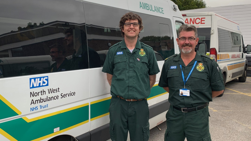Two men stood in NWAS uniform stood in front of Patient Transport Service ambulance.