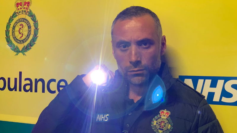 Senior Paramedic Luca holding up a torch with ambulance backdrop