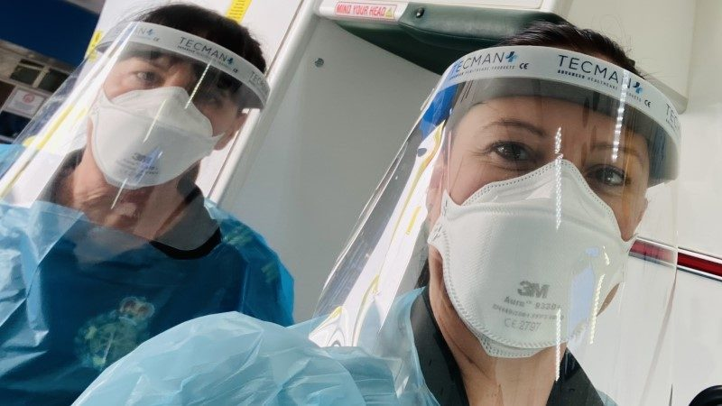 Mother and daughter clinicians wearing PPE face masks, visors and aprons
